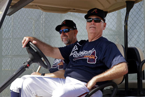 Atlanta Braves manager Brian Snitker, right, and bench coach Walt Weiss watch from a golf cart as the pitchers and catchers get loose during spring training baseball camp Thursday, Feb. 13, 2020, in North Port, Fla. (AP Photo/John Bazemore)