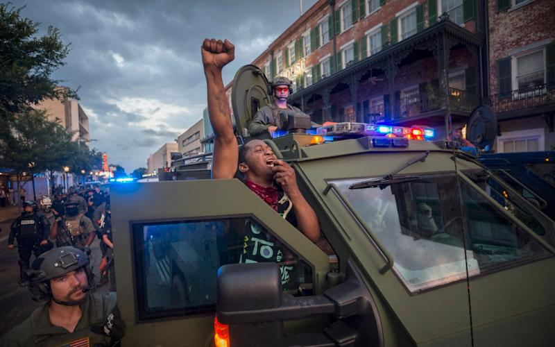 SWAT vehicles have become more commonplace across American streets as part of the effort to contain riots - Stephen B Morton/Atlanta Journal-Constitution