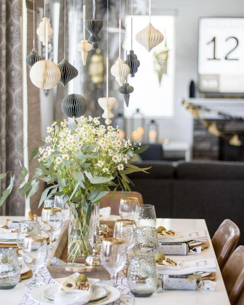 """<p>Hang paper lanterns above the table for a throwback to traditional lantern centerpieces without the hazard. Suspended over fresh flowers, <a href=""""https://www.instagram.com/p/CNgAa6TjRm0/"""" rel=""""nofollow noopener"""" target=""""_blank"""" data-ylk=""""slk:Lubdna Dadabhoy"""" class=""""link rapid-noclick-resp"""">Lubdna Dadabhoy</a> imparts plenty of dramatic atmosphere in a smaller space.</p>"""