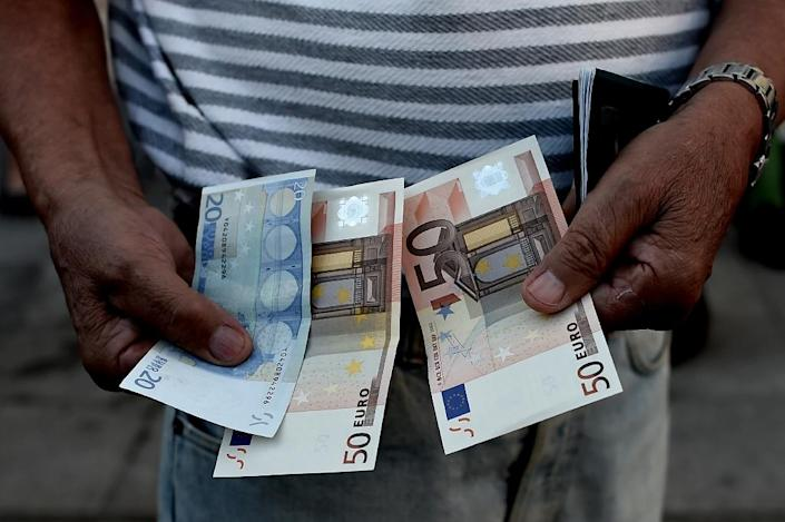A Greek pensioner holds 120 euros outside a national bank branch in Athens, on July 1, 2015 (AFP Photo/Aris Messinis)