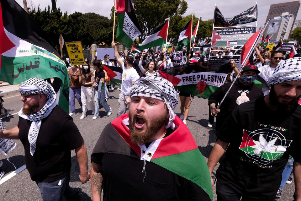 Demonstrators holding signs march to Israeli Consulate during a protest against Israel and in support of Palestinians, Saturday, May 15, 2021 in the Westwood section of Los Angeles. (AP Photo/Ringo H.W. Chiu)