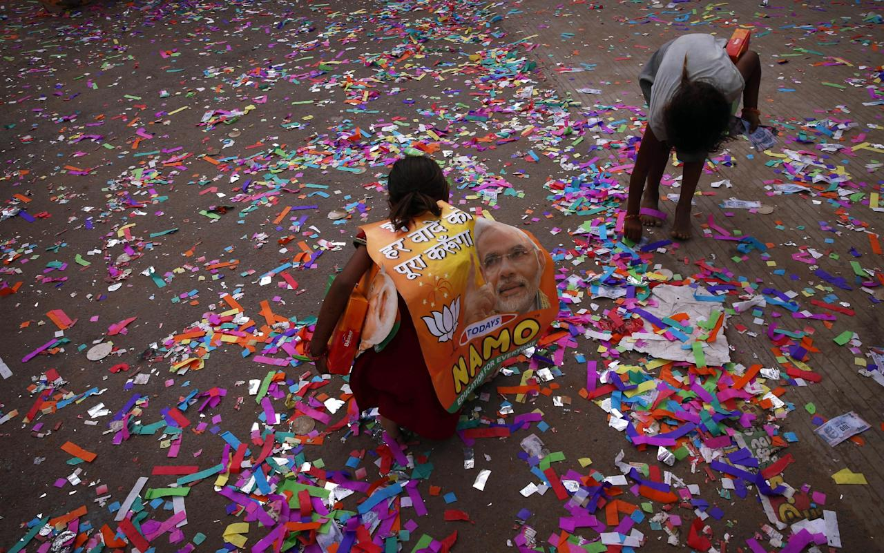 Ragpicker children pick currency notes from the ground after they were thrown in an act of jubilation by supporters of the Opposition Bharatiya Janata Party (BJP) outside the party office in Gandhinagar, in the western Indian state of Gujarat, Friday, May 16, 2014. Modi and his party won national elections in a landslide Friday, preliminary results showed, driving the long-dominant Congress party out of power in the most commanding victory India has seen in more than a quarter century. The Hindu nationalist Bharatiya Janata Party captured a commanding lead for at least 272 seats in the lower house of Parliament, the majority needed to create a government without forming a coalition with smaller parties. (AP Photo/Saurabh Das)