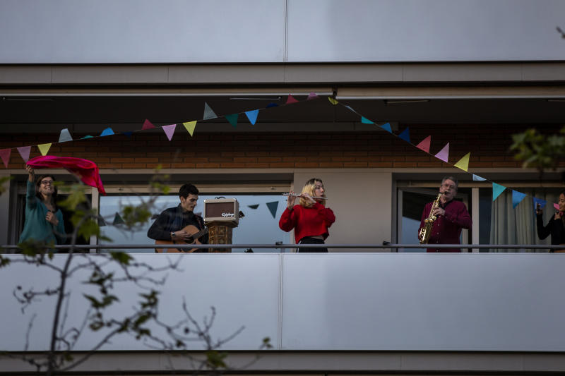 "Family members play their instruments performing the song ""Aleluya"" on their balcony in support of the medical staff that are working on the COVID-19 virus outbreak in Barcelona, Spain, Sunday, April 5, 2020. Spanish Prime Minister Pedro Sanchez announced that he would ask the Parliament to extend the state of emergency by two more weeks, taking the lockdown on mobility until April 26. The new coronavirus causes mild or moderate symptoms for most people, but for some, especially older adults and people with existing health problems, it can cause more severe illness or death. (AP Photo/Emilio Morenatti)"