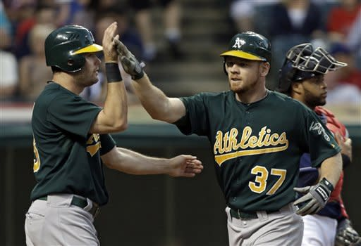 Oakland Athletics' Brandon Moss (37) is greeted by Seth Smith after Moss's two-run home run off Cleveland Indians starting pitcher Zach McAllister in the third inning of a baseball game Tuesday, Aug. 28, 2012, in Cleveland. (AP Photo/Mark Duncan)