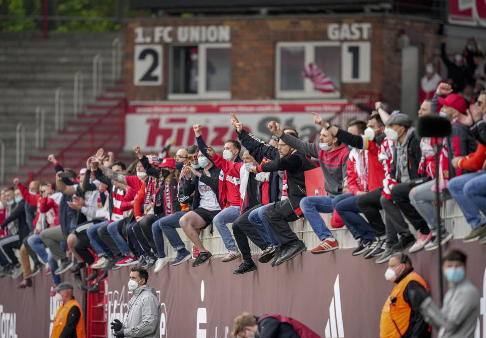 Union fans cheer for their team after the German Bundesliga soccer match between 1. FC Union Berlin and RB Leipzig in Berlin, Germany, Saturday, May 22, 2021. (AP Photo/Michael Sohn, pool)