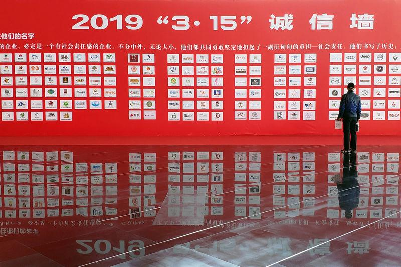 "Man stands in front of an ""integrity wall"" at a consumer goods expo which opens a day ahead of World Consumer Rights Day, in Dalian"
