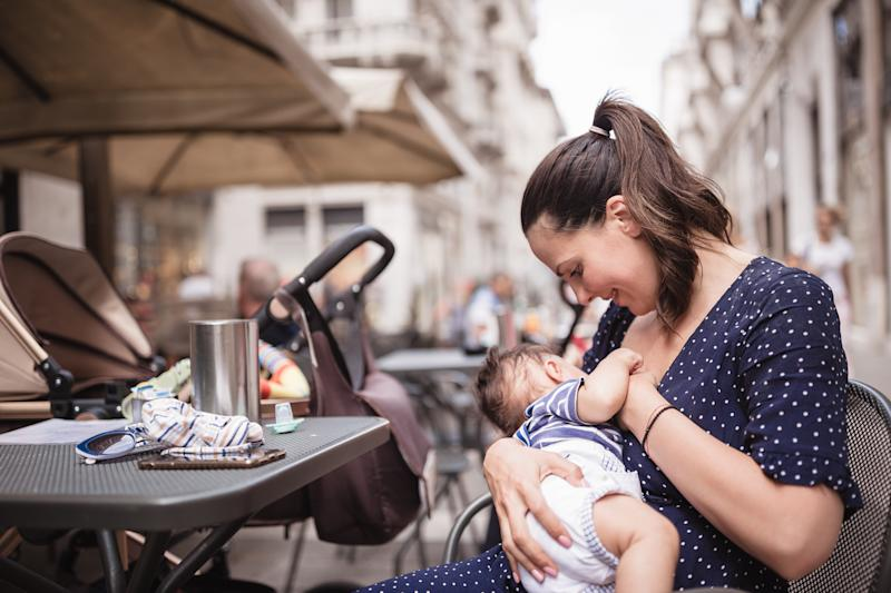 Young mother breastfeeding her baby boy in public place. Trieste, Italy, Europe