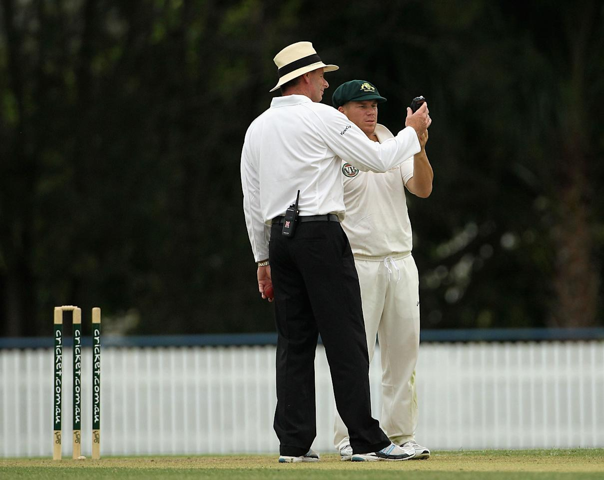 BRISBANE, AUSTRALIA - NOVEMBER 24:  David Warner (R) of Australia A checks the light meter with umpire Paul Reiffel as bad light stops play during day one of the International Tour Match between Australia A and New Zealand at Allan Border Field on November 24, 2011 in Brisbane, Australia.  (Photo by Hamish Blair/Getty Images)