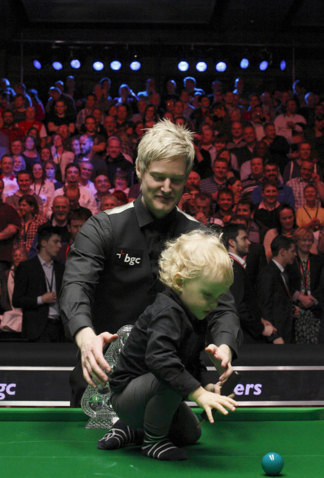 Australia's Neil Roberts looks after his son Alexander after winning winning over England's Shaun Murphy in the BGC Masters snooker final at Alexandra Palace in London on January 22, 2012. Australia's 2010 world champion Neil Robertson claimed the Masters title with a 10-6 win over England's Shaun Murphy at Alexandra Palace. AFP PHOTO / JUSTIN TALLIS (Photo credit should read JUSTIN TALLIS/AFP/Getty Images)