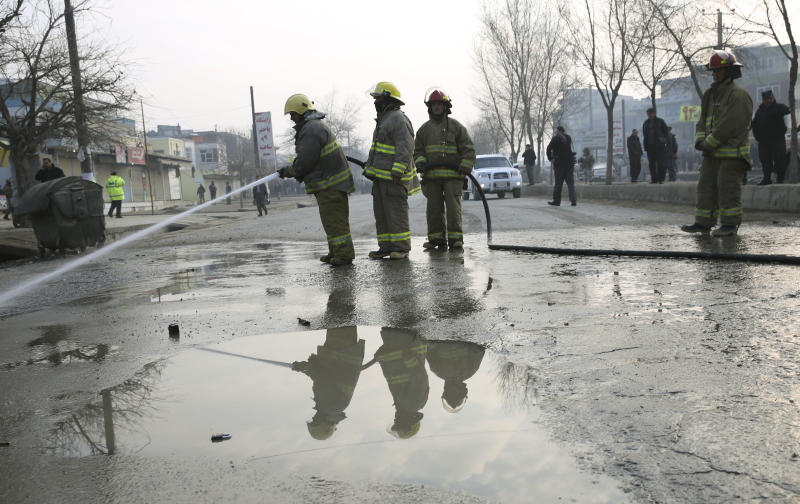 Afghan firefighters clean the site of a suicide attack in Kabul, Afghanistan, Sunday, Jan. 26, 2014. An Afghan official said a suicide bomber attacked a military bus in Kabul, killing at least four people. (AP Photo/Massoud Hossaini)
