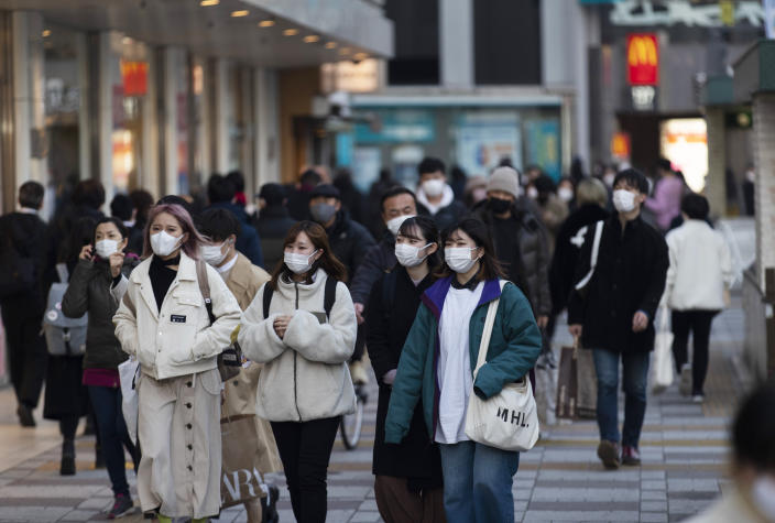 People wearing face masks walk by a train station during a coronavirus state of emergency in Tokyo on Thursday, Jan. 14, 2021. (AP Photo/Hiro Komae)