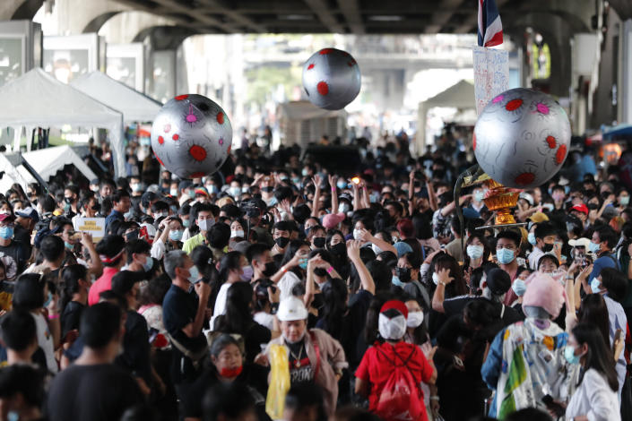 """Large balls that depict asteroids are thrown in the air over a crowd attending a student rally in Bangkok, Saturday, Nov. 21, 2020. Organized by a group that mockingly calls themselves """"Bad Students,"""" the rally calls for educational reforms and also supports the broader pro-democracy movement's demands for constitutional change. (AP Photo/Sakchai Lalit)"""
