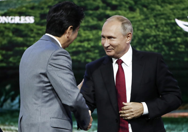 Russian President Vladimir Putin, right, shakes hands with Japanese Prime Minister Shinzo Abe during a plenary session at the Eastern Economic Forum in Vladivostok, Russia, Wednesday, Sept. 12, 2018. (Valery Sharifulin/TASS News Agency Pool Photo via AP)