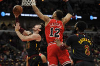 Cleveland Cavaliers' Cedi Osman (16) goes up for a shot against Chicago Bulls' Daniel Gafford (12) during the first half of an NBA basketball game Tuesday, March 10, 2020, in Chicago. (AP Photo/Paul Beaty)