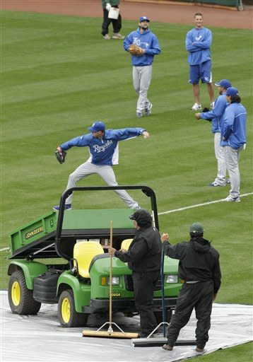 Groundskeepers watch the Kansas City Royals warm up as they prepare to remove water from the field prior to the baseball game against the Oakland Athletics Tuesday, April 10, 2012, in Oakland, Calif. (AP Photo/Ben Margot)