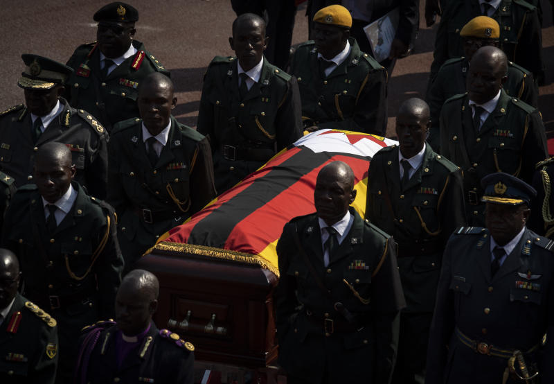 The casket of former president Robert Mugabe is escorted by military officers as it departs after a state funeral at the National Sports Stadium in the capital Harare, Zimbabwe Saturday, Sept. 14, 2019. African heads of state and envoys gathered to attend a state funeral for Zimbabwe's founding president, Robert Mugabe, whose burial has been delayed for at least a month until a special mausoleum can be built for his remains. (AP Photo/Ben Curtis)