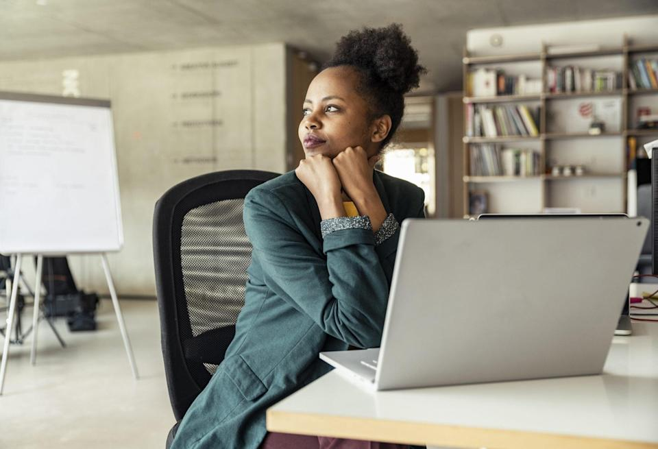 woman at desk looking off in distance