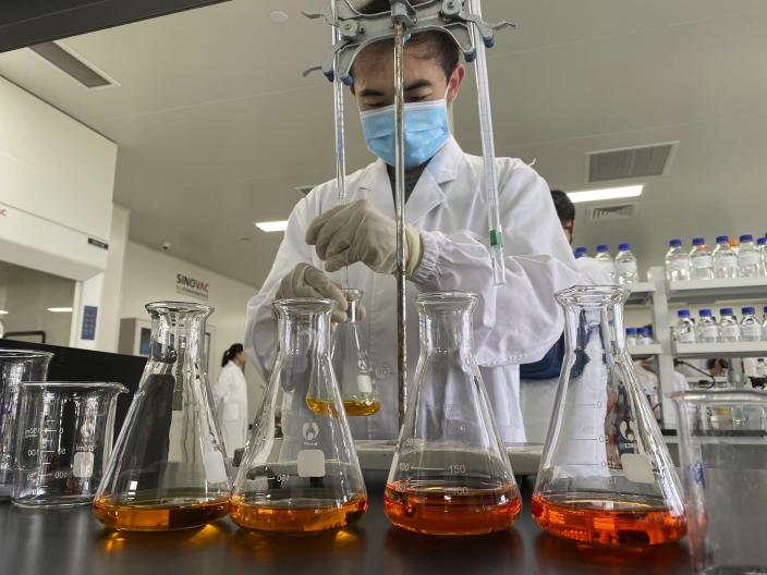 A worker works inside a lab at the SinoVac vaccine factory in Beijing on Thursday, Sept. 24, 2020. SinoVac, one of China's pharmaceutical companies behind a leading COVID-19 vaccine candidate says its vaccine will be ready by early 2021 for distribution worldwide, including the U.S. (AP Photo/Ng Han Guan)