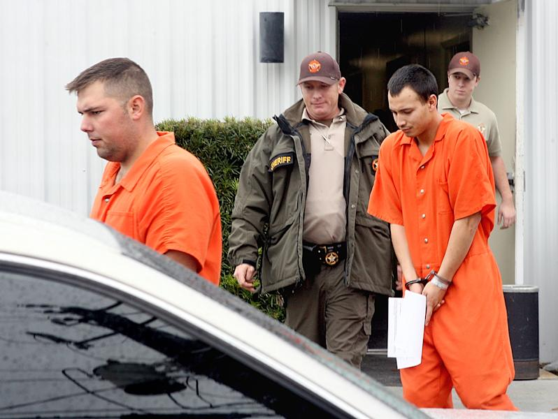 FILE - In this Dec. 12, 2011 file photo, U.S. Army Sgt. Anthony Peden, 25, left, and Pvt. Isaac Aguigui, 19, are led away in handcuffs after appearing before a magistrate judge at the Long County Sheriffs Office in Ludowici, Ga. Prosecutors say a murder case against the four soldiers in Georgia has revealed they formed an anarchist militia within the U.S. military with plans to overthrow the federal government, The Associated Press reports Monday, Aug. 27, 2012. (AP Photo/Lewis Levine, File)