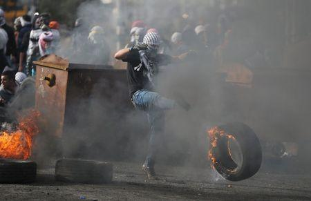 A Palestinian protester kicks a burning tyre during clashes with Israeli troops near the Jewish settlement of Bet El, near the West Bank city of Ramallah, October 29, 2015. REUTERS/Mohamad Torokman