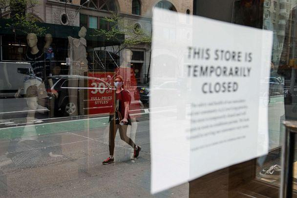 PHOTO: A woman wearing personal protective equipment walks past a closed J. Crew store on May 4, 2020 in New York. (Bryan Thomas/Getty Images)
