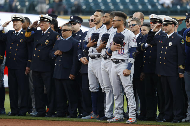 Houston Astros' Carlos Correa, from left, Josh James and Yuli Gurriel (10) stand with first responders during the national anthem before a baseball game against the Detroit Tigers in Detroit, Tuesday, Sept. 11, 2018. (AP Photo/Paul Sancya)
