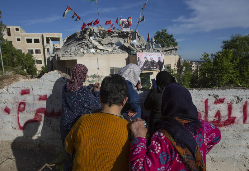 Palestinian women look at the building that was partly demolished by the Israeli army, in the West Bank village of Kobar, near Ramallah, Monday, May 11, 2020. The Israeli army demolished the top floor of the two story building that belongs to the Barghouti family during an overnight operation in the village. Israel says 22-year-old Qassem Barghouti carried out the attack in August, which killed 17-year-old Israeli Rina Shnerb and wounded her father and brother as they were hiking down to a spring in the West Bank near the settlement of Dolev. (AP Photo/Nasser Nasser)