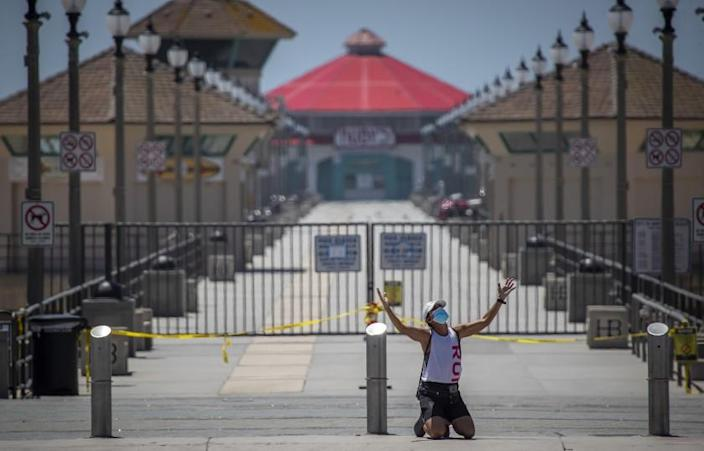 """HUNTINGTON BEACH, CA -- WEDNESDAY, APRIL 22, 2020: Denise Martinez, of Costa Mesa, kneels down in prayer in front of the closed Huntington Beach pier as she spreads her message of love, not the anarchy that she says some of the stay-at-home protesters want. """"I'm out here praying for the city,"""" Martinez said. """"And to show an example of Christ, who is love. Our freedom doesn't come from a spirit of anarchy. Right now our main focus is loving each other at any cost. The lord says today that he hears the cries of his people and to trust him. Because love overcomes everything."""" Beach-goers enjoyed warm summer-like weather amid state and city social distancing regulations to stave off Coronavirus mandated by Gov. Newsom in Huntington Beach, CA, on April 22, 2020. (Allen J. Schaben / Los Angeles Times)"""
