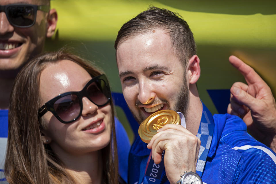 CORRECTS NAME TO ARTEM DOLGOPYAT - Artem Dolgopyat, Israeli artistic gymnastics men's gold medalist of Tokyo 2020, stands with his partner Maria Masha Sakovichas, while holding his medal on his arrival to Ben Gurion Airport, near Tel Aviv, Israel, Tuesday Aug. 3, 2021. The Ukrainian-born Israeli gymnast was hailed as a national hero for winning Israel's second-ever gold medal — and its first in artistic gymnastics. But the celebrations were tempered after his mother lamented that the country's authorities will not allow him to wed because he is not considered Jewish according to Orthodox law. (AP Photo/Ariel Schalit)