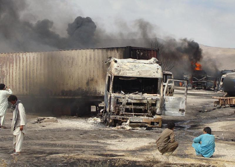 Burning NATO supply trucks are seen in Samangan, north of Kabul, Afghanistan, Wednesday, July 18, 2012. Afghan officials say a magnetic bomb placed on a truck exploded and destroyed 22 NATO supply vehicles in northern Afghanistan. (AP Photo/Javed Basharat)