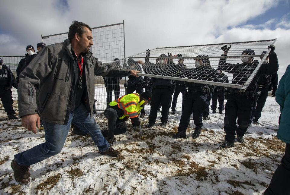 A man pulls a metal barrier while police hold onto it.