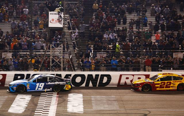 Martin Truex Jr. crosses the finish line in front of Joey Logano Saturday night. (AP Photo/Steve Helber)