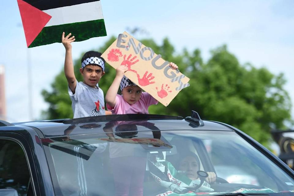 Children in a passing car held signs for KC Rally as Palestinians and supporters gathered Saturday, May 15, on the Country Club Plaza to show support for Palestinian human rights and to condemn violence against Palestinians in Gaza and the Middle East.