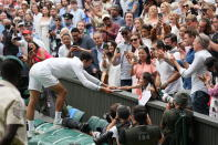 Serbia's Novak Djokovic presents his tennis racquet to a young fan after winning the men's singles final against Italy's Matteo Berrettini on day thirteen of the Wimbledon Tennis Championships in London, Sunday, July 11, 2021. (AP Photo/Alberto Pezzali)