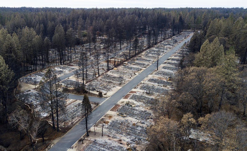 """FILE - In this Monday, Dec. 3, 2018, homes are seen leveled by the Camp Fire line the Ridgewood Mobile Home Park retirement community in Paradise, Calif. An Associated Press review shows widespread problems with the four """"public safety power shutoffs"""" the utility started rolling out in 2018, a year before massive blackouts paralyzed much of California in recent months. Interviews and documents obtained under public records requests reveal persistent failures and broken promises that in some cases compromised public safety. (AP Photo/Noah Berger,File)"""