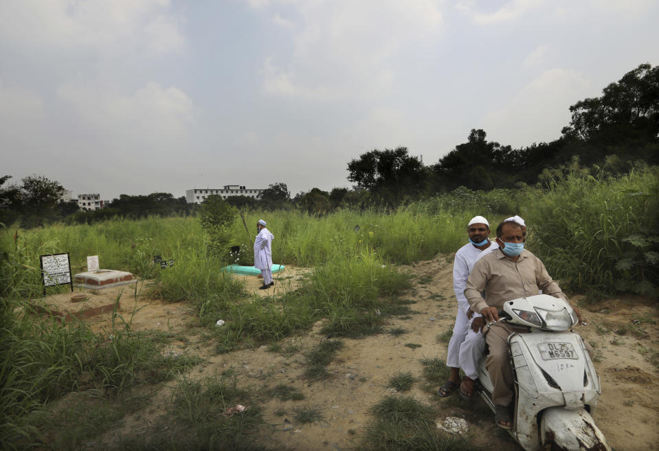 An Indian Muslim man looks for the grave of his relative who died of coronavirus in New Delhi, India, Wednesday, Sept. 16, 2020. India is now second in the world with the number of reported coronavirus infections with over 5.1 million cases, behind only the United States. Its death toll of only 83,000 in a country of 1.3 billion people, however, is raising questions about the way it counts fatalities from COVID-19. (AP Photo/Manish Swarup)