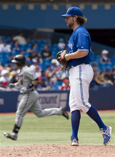 Toronto Blue Jays starting pitcher R.A. Dickey stands on the mound as Minnesota Twins' Brian Dozier rounds the bases on a three-run home run during the seventh inning of a baseball game in Toronto on Saturday, July 6, 2013. (AP Photo/The Canadian Press, Frank Gunn)