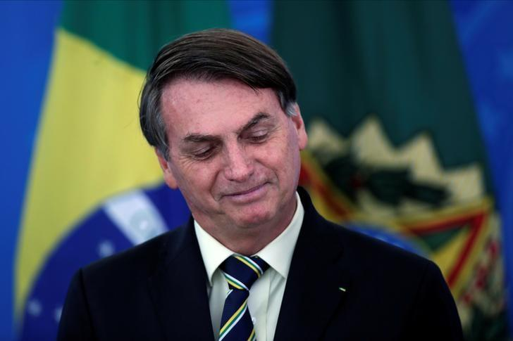 Brazil's President Bolsonaro smiles at a media statement in Brasilia