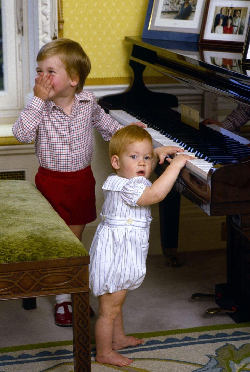 """<p>Prince William giggles while his brother Prince Harry fiddles with some keys on the piano at their home in Kensington Palace. The princes, who have lived in separate apartments within the palace over the years, have maintained a close relationship. Shortly after Harry announced his engagement in November 2017, <a href=""""https://twitter.com/KensingtonRoyal/status/935908818118217728"""" rel=""""nofollow noopener"""" target=""""_blank"""" data-ylk=""""slk:William told reporters"""" class=""""link rapid-noclick-resp"""">William told reporters</a>, """"For me personally, I hope it means he stays out of my fridge and stop him scrounging over my food like he's done over the last few years. I'm pretty excited.""""</p>"""