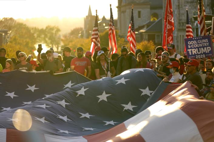 Supporters of President Donald Trump unfurl a giant American flag outside the Pennsylvania State Capitol after Democrat Joe Biden defeated Trump to become 46th president of the United States.