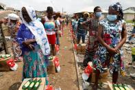 Women queue for food parcels during distribution by volunteers of the Lagos food bank initiative in a community in Oworoshoki, Lagos,