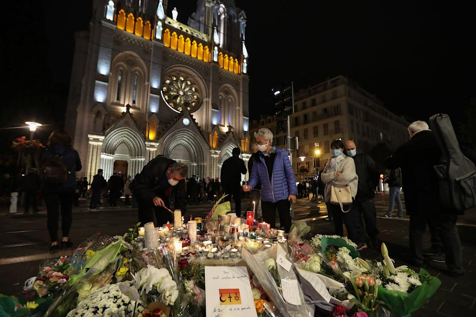 People light candles outside Notre-Dame de l'Assomption Basilica in Nice on October 31, 2020, to pay tribute to the victims two days after a knife attacker killed three people, cutting the throat of two, inside the church of the French Riviera city, and police arrest a young Tunisian migrant from Sfax who arrived in Europe only last month, according to French prosecutors. - The killings came two weeks after a French teacher was decapitated outside his school north of Paris by a suspected Islamist extremist. The teacher had shown his pupils cartoons of the Prophet Mohammed during a lesson on freedom of speech. (Photo by Valery HACHE / AFP) (Photo by VALERY HACHE/AFP via Getty Images)