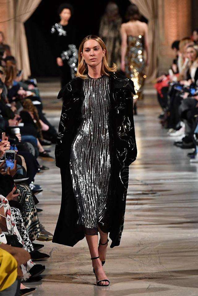 <p>A silver sequined dress and black coat at the Oscar de la Renta FW18 show. (Photo: Getty) </p>