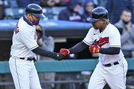 Cleveland Indians third base coach Mike Sarbaugh congratulates Jose Ramirez after Ramirez hit a solo home run in the fourth inning of a baseball game against the Chicago Cubs, Tuesday, May 11, 2021, in Cleveland. Cleveland won 3-2. (AP Photo/Tony Dejak)