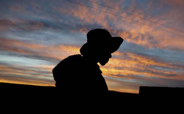 """Mayor Rufino Choque is silhouetted against a sunset sky in the Urus del Lago Poopo Indigenous community, in Punaca, Bolivia, Sunday, May 23, 2021. """"Our grandfathers thought the lake would last all their lives, and now my people are near extinction because our source of life has been lost,"""" said Luis Valero, leader of the Uru communities around Lake Poopo, Bolivia's second-largest lake that dried up about five years ago. (AP Photo/Juan Karita)"""