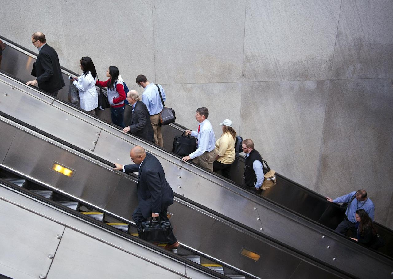 People exit a Metro subway station, by escalator, along Pennsylvania Ave., NW, in Washington, Thursday, Oct. 17, 2013. After 16 days of being off the job, thousands of furloughed federal workers are returning to work now that the government shutdown has been resolved. (AP Photo/Cliff Owen)