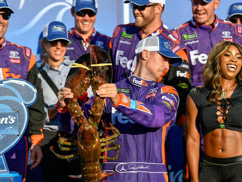 Denny Hamlin reacts as he holds a lobster winning at New Hampshire Motor Speedway in 2017.