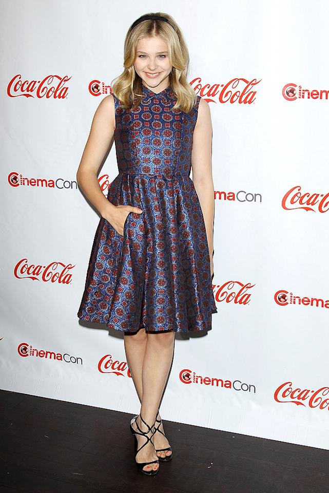 "Following in Theron's footsteps was the always adorable Chloe Moretz (<a target=""_blank"" href=""http://movies.yahoo.com/movie/dark-shadows/"">""Dark Shadows""</a>), who nearly stole the spotlight in a sleeveless Kenzo cocktail frock and strappy Jimmy Choo ""Lance"" sandals. (4/26/2012)"