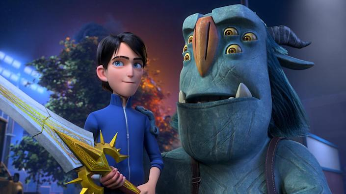 An animated boy holds a huge sword next to a blue troll with many eyes.