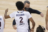 Virginia guard Reece Beekman (2) gets a hug from head coach Tony Bennett after sinking the game winning shot during the second half of an NCAA college basketball game against Syracuse in the quarterfinal round of the Atlantic Coast Conference tournament in Greensboro, N.C., Thursday, March 11, 2021. Virginia defeated Syracuse 72-69.(AP Photo/Gerry Broome)